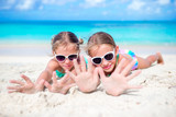 Little girls having fun at tropical beach playing together at shallow water. Adorable little sisters at beach during summer vacation