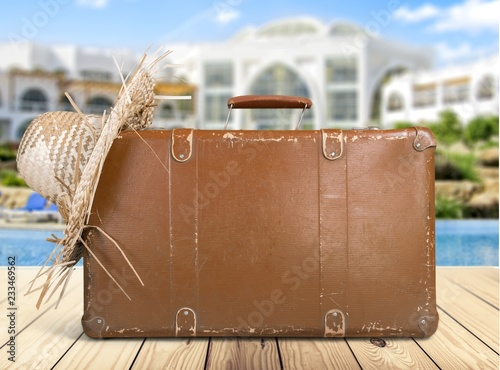 Foto Murales Retro suitcase with travel hat on wooden background