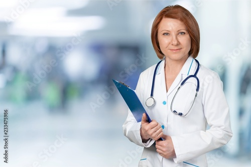 Leinwandbild Motiv Attractive young female doctor with blurred hospital interior on