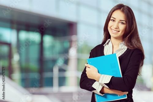 Młoda uśmiechnięta kobieta trzyma błękitnego notatnika