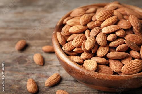 Leinwandbild Motiv Tasty organic almond nuts in bowl on table