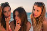 Tres bellas y picaras mujeres muy sexys lanzando besos sobre la arena de una playa del caribe. © ismel leal