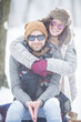 Leinwandbild Motiv Young couple in front of a camera in snow outdoors