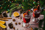 Two glasses of Christmas mulled wine with spices and orange slices on a wooden rustic table. A traditional drink for the winter holidays