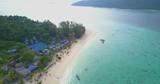 High altitude, high key aerial view of white sand beach and crystal clear tropical ocean hugging coastline of Ko Lipe, Thailand. 4k 1.9:1 23.976fps - 233495348