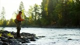 Fisherman using rod and reel casting line in freshwater river  - 233498778