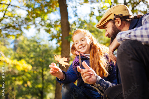 Leinwandbild Motiv Autumn season. Cute red haired girl holding an orange leaf while sitting together with her dad