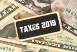 Dollar Geldscheine und ein Schild Steuern 2019