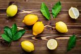 Fresh lemons and  lemons leaves on shabby wooden background. - 233503722