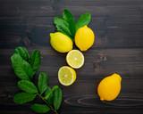 Fresh lemons and  lemons leaves on dark wooden background. - 233503791
