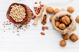 Various legumes and different kinds of nuts set up on white wooden table. - 233503905