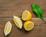 Fresh lemons and  lemons leaves on rustic wooden background. Fresh lemons and lemon slice on wooden table with flat lay.  Fresh citrus fruit background. - 233504135
