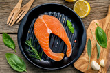 Salmon fillet in old cast iron skillet on wooden background. Ingredients for making steak. Various herbs and seasoning rosemary ,sage leaves ,basil ,garlic and peppercorn. - 233504154