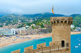 Old tower and stone fortress walls against background of resort town of Tossa de Mar, Costa Brava, Spain