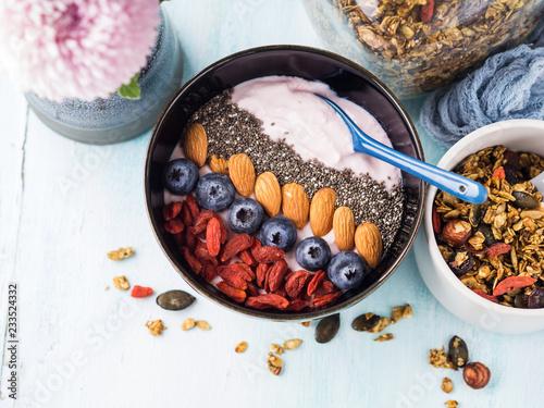 Leinwandbild Motiv Yogurt raspberry smoothie bowl with goji berries and blueberries, almonds, chia seeds and granola on pastel turquoise wooden background. Plant based breakfast