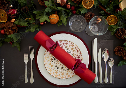 Leinwandbild Motiv Christmas table setting with a red Christmas cracker arranged on a plate and green and red table decorations, overhead view
