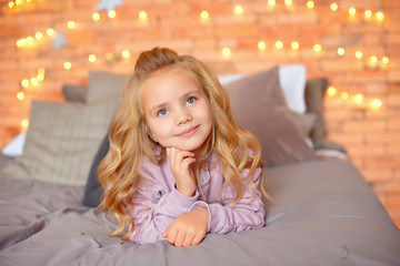 Beautiful girl with blond curls in anticipation of gifts in the background Christmas lights and bed . New Year and Christmas concept. © Viktoria