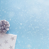 A blue Christmas copy space card with snowflakes, white present in the stars and a pine cone - 233538140
