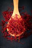 Saffron spice threads (strands) in wooden spoon on black background - 233539195