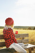 A young woman from behind in red plaid shirt with a wool cap and scarf taking a cup of tea or coffee while she is sunbathing sitting in a wooden bench in a yellow field with backlight from autumn sun