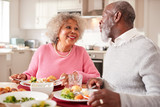 Senior black couple smiling to each other as they eat Sunday dinner together at home, close up - 233553739