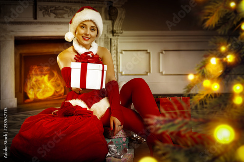 Leinwandbild Motiv Slim young santa claus woman with christmas tree decoration and background of fireplace