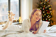 holidays and people concept - happy young woman writing to notebook or making wish list in bed at home over christmas tree lights on background
