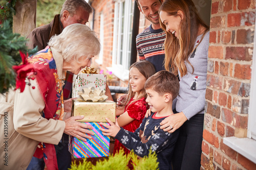 Leinwandbild Motiv Grandparents Being Greeted By Family As They Arrive For Visit On Christmas Day With Gifts