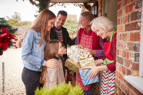 Leinwandbild Motiv Family Being Greeted By Grandparents As They Arrive For Visit On Christmas Day With Gifts