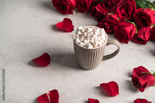 hot chocolate topped with marshmallow, red roses on grey marble surface, romantic mood