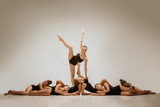 The group of modern ballet dancers dancing on gray studio background - 233572761