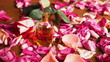 Aroma oil glass bottle among roses petals on the table, natural raw material, selected focus