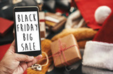 Black Friday big sale text on phone screen. Special discount christmas offer sign. Big Sales. Hand holding phone with advertising message at credit cards, bags, clothes, gifts.
