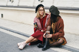 Two friends with coffee to go in casual warm outfits outdoors po - 233605120