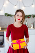 beautiful white girl holding a gift box in her hands against the background of the scenery for Christmas in the kitchen