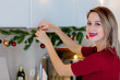 beautiful white woman preparing a Christmas tree branch and baubles at kitchen