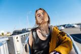 Young beautiful woman wearing yellow jacket standing on the bridge © Viacheslav Iakobchuk