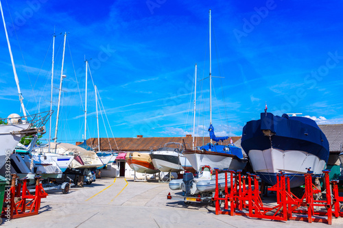 Boats and yachts for repair in a dry dock. Wonderful romantic summer at sea.