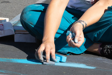 Street artist using chalk to draw on the pavement.