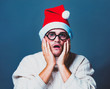 Funny man in red Christmas hat and white sweater and glasses