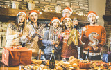 Friends group with santa hat celebrating Christmas time with champagne and sweets food at dinner party - Winter holiday concept with people enjoying each other having fun eating together - Warm filter