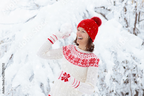 Leinwandbild Motiv Woman in sweater playing snow ball fight in winter