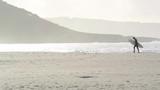 Hombre con tabla de surf en la playa - 233709975