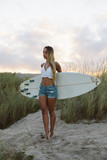 Young beautiful surfer standing at the beach with her surfboard in the morning. Natural girl on her way to the sea for surfing. Playa de Salinas, Asturias, Spain. - 233713530