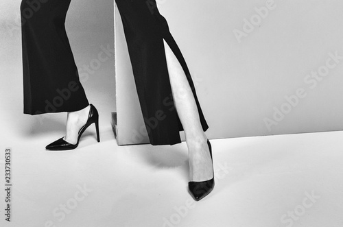 Black and white shot of Cropped shot of fashionable woman in high heels standing near wall