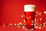 Pale ale or beer in pint glass with christmas lights and tinsel on red background - 233734101
