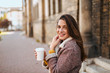Young woman in the street drinking coffee.