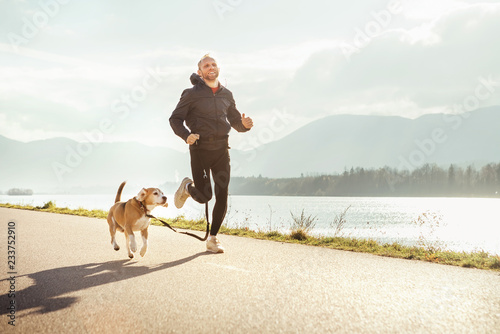 Leinwandbild Motiv Morning jogging with pet: man runs together with his beagle dog