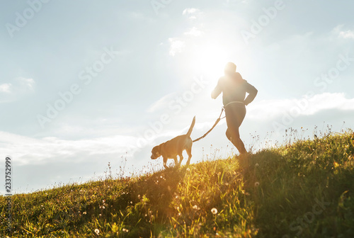 Leinwanddruck Bild Bright sunny Morning Canicross exercises. Man runs with his beagle dog.