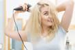Blonde woman using hair dryer